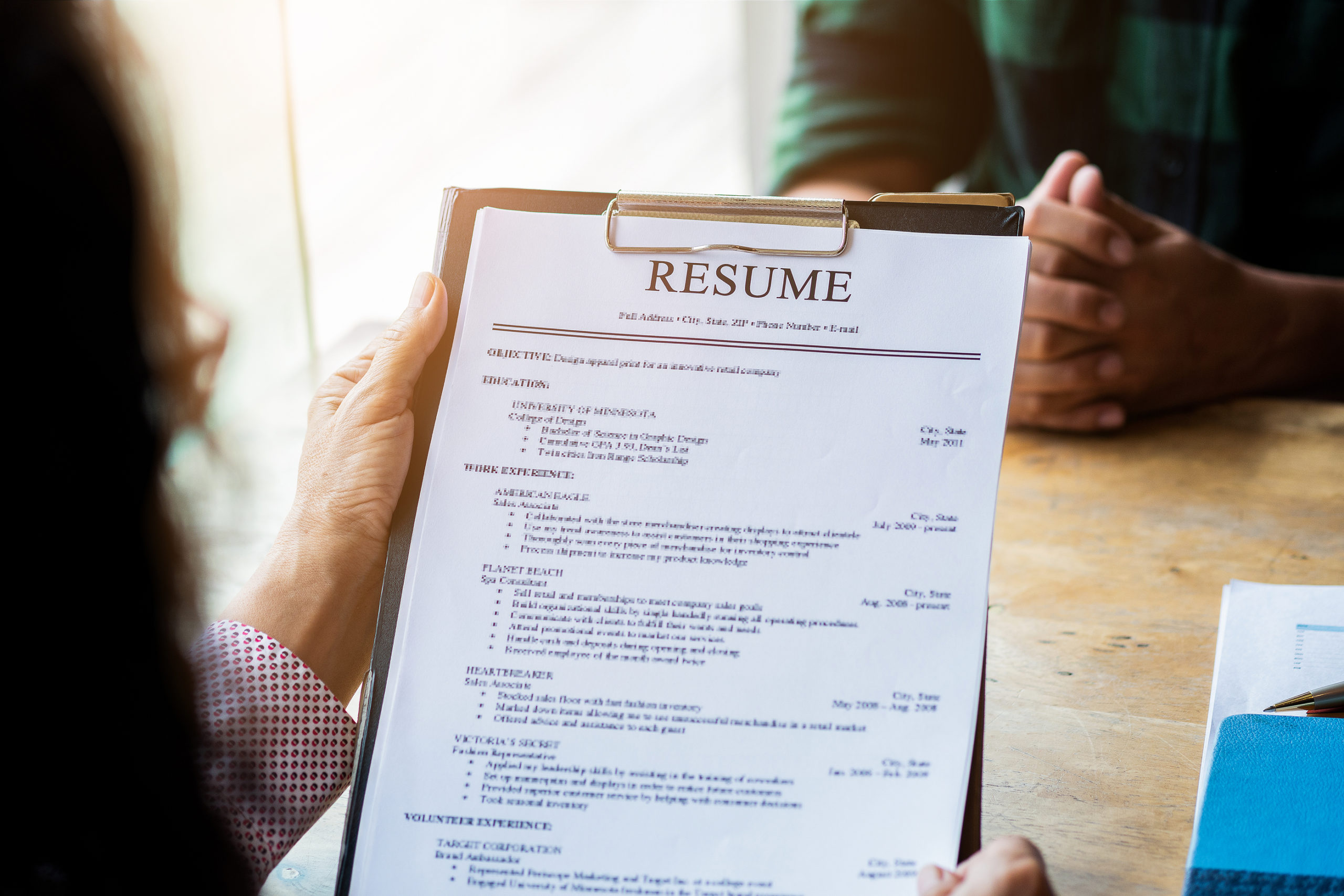 Interviewer reading an IT job resume, Person submits job application, Person describe yourself to interviewer, Close up view of job interview in office, focus on resume, recruiter considering application, hr manager making hiring decision
