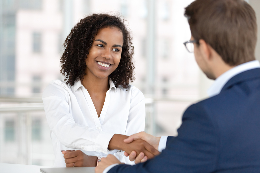 Smiling HR manager giving a handshake to a IT contract staffing candidate at job interview.