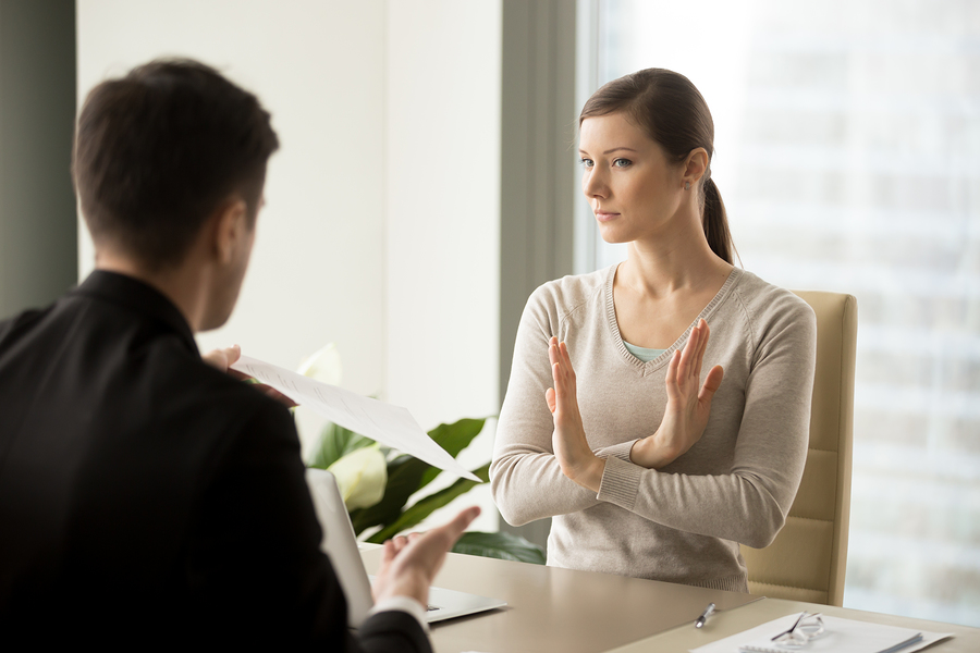 Skeptical young woman rejecting counter offer from current employer when sitting at desk in front of a manager.