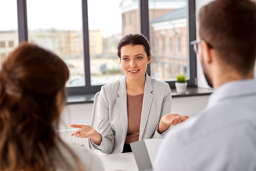 Tech staffing agency recruiters having interview with female employee at office.