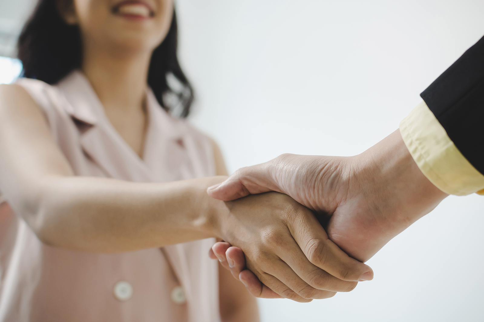 Young Woman Shaking Hands with Employer over Successful Contract Negotiations